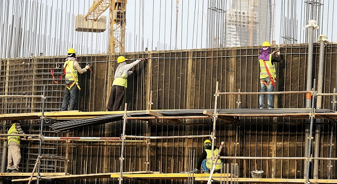 Indian labourers work at the construction site of a building in Riyadh